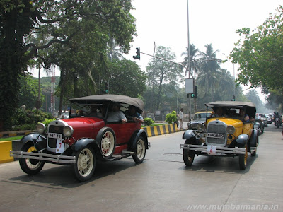 two similar vintage cars driving side by side