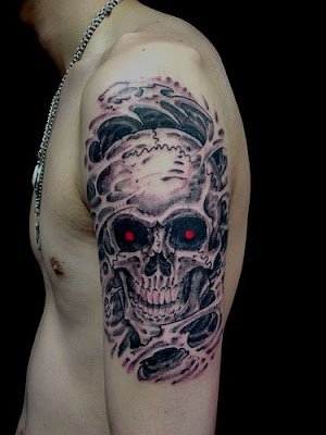 Flaming skull forearm tattoo.