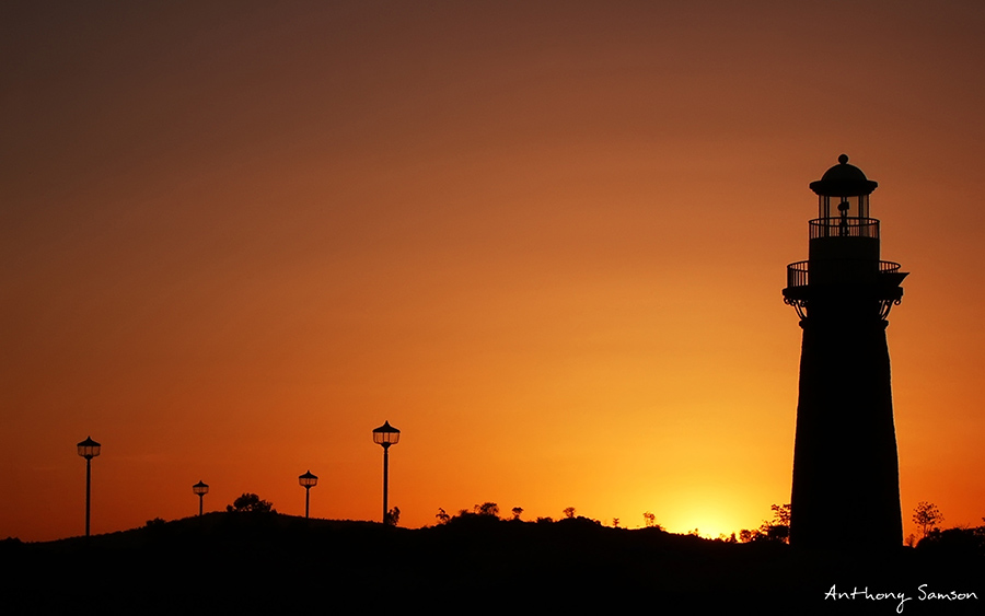 Beautiful sunset photo with light house as silhoute