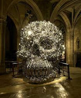 A huge skull crafted out of aluminum pots and pans