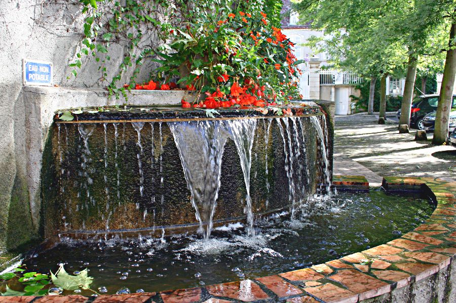 wall with two-level fountain and red geraniums