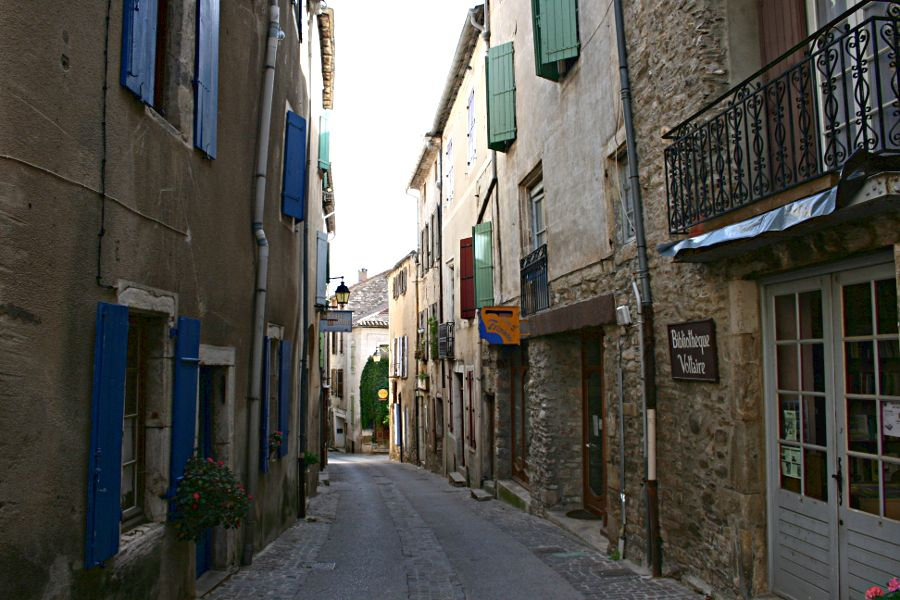 narrow shady street with tall houses and shutters