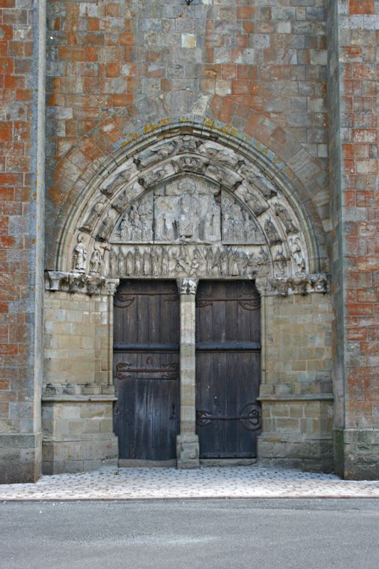 old and patched church door with tympanum