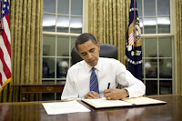 President Obama at his desk signing papers
