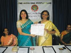 Mrs. Hegde presents the OIOP Club Membership Certificate to Mrs. Sinkar