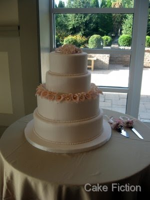 An elegant four tier wedding cake in ivory fondant surrounded by a ring of