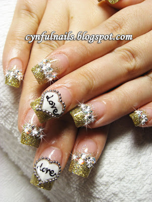 This is an eye-catching and sparkly set of gold nails! The heart design is