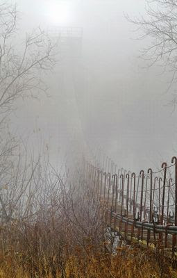 Пешеходный подвесной мост в густом тумане.