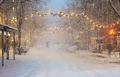 Новогодние зимние мотивы на улицах заснеженного города. Снег идет, красивые гирлянды украшают улицу города. Одинокий прохожий на заснеженной улице города. Снегопад зимой в городе перед Новым Годом фото.