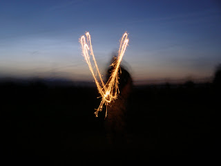 A shadowy figure drawing a V with a sparkler