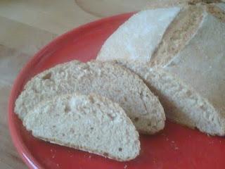 Hogaza de pan en pirex con dos rebanadas cortadas.