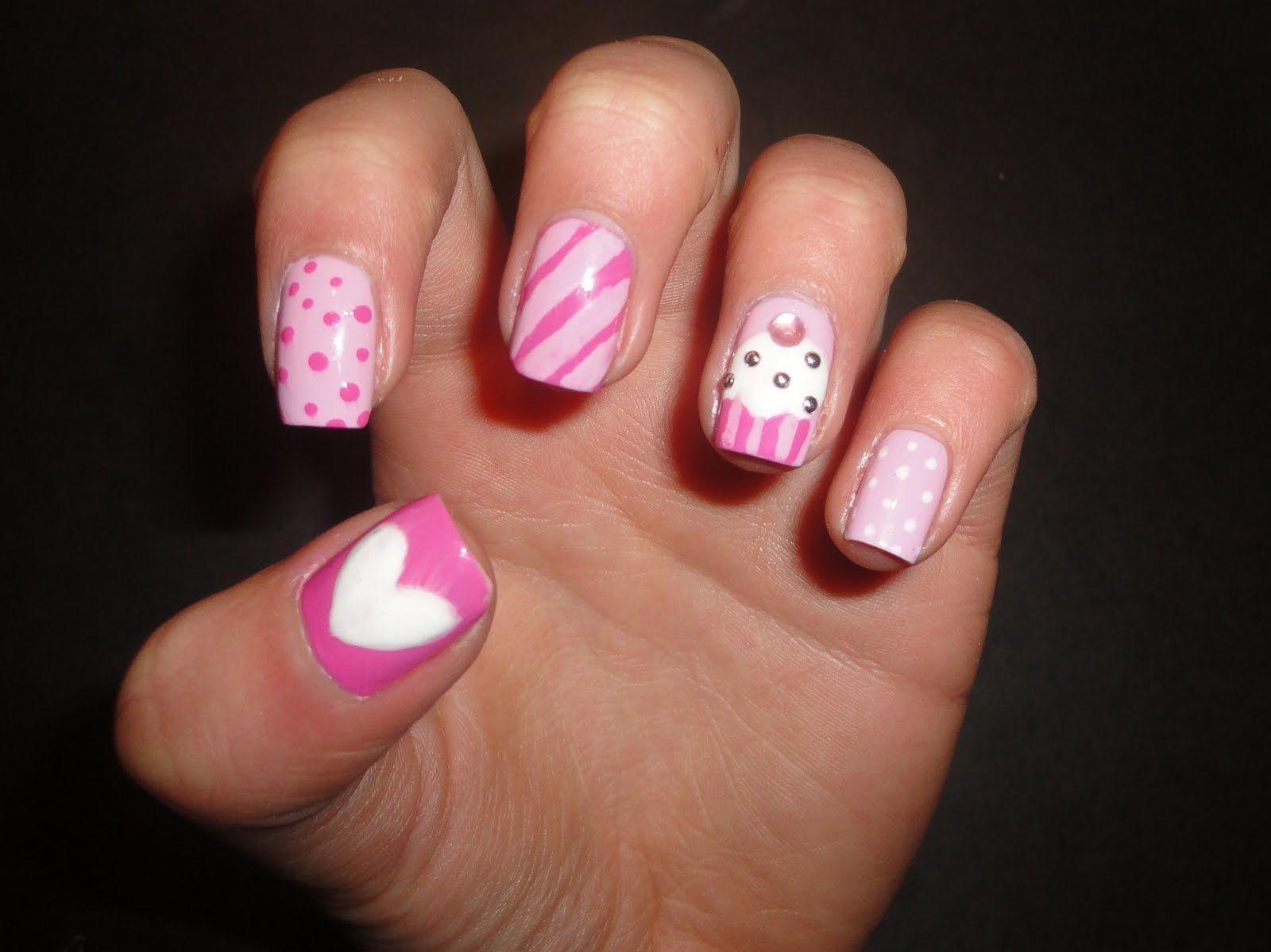 yummy creamy and delicious pink white candies and cupcakes on nails