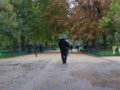 Man walking with an umbrella at Monceau Park