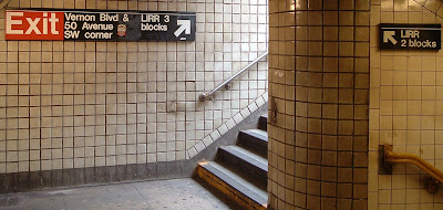 A sign on the wall adjacent to the top of a set of stairs from below reads, LIRR: 2 blocks. An exit sign on the wall near the bottom of a second set of stairs leading to the surface includes, LIRR: 3 blocks.