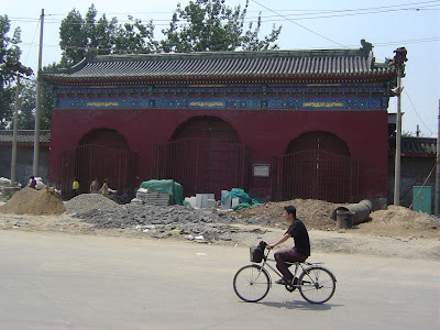 guy bikes past ruins of building