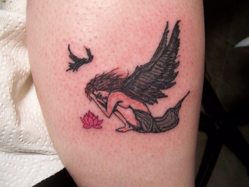 Grieving angel with flower tattoo.