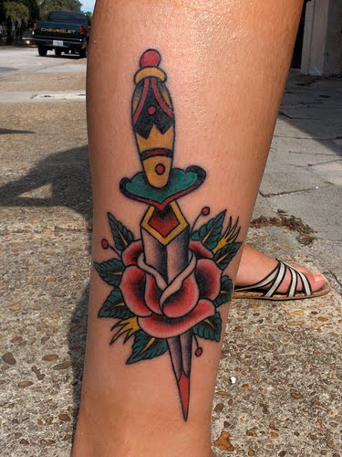 Colorful rose and dagger tattoo on lower leg.