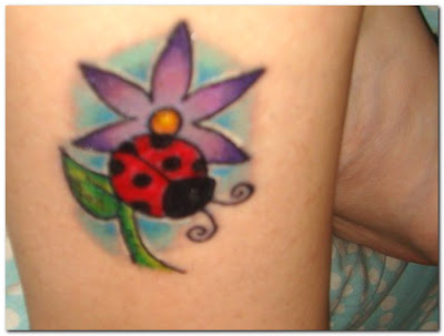 Comments: Flower, ladybug, and name on a hip. Flower and ladybug tattoo.