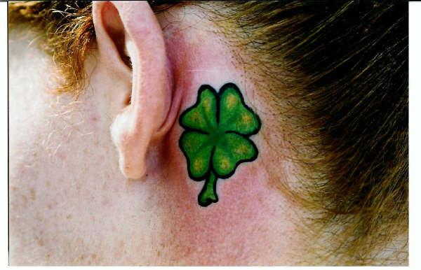 This picture shows the green four leaf clover tattoo with