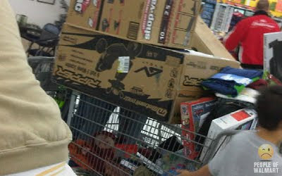 baby in shopping cart under a lot of big walmart purchases