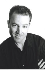 Jack Boucher in medium close-up, arms crossed across his black shirt, short hair, smiling.