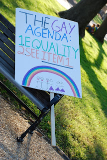 protest sign with rainbow that says The Gay Agenda: 1. Equality 2. See Item 1