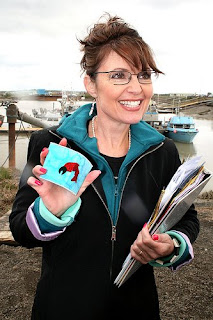 Sarah Palin holding something and looking out of it