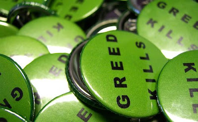 pile of buttons that say Greed Kills