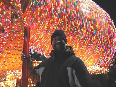 man standing in front of cement mixer covered with Christmas lights