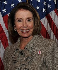 a sinister looking Nancy Pelosi posing in front of an American flag