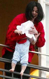 Michael acena com seu filho do lado de fora da sacada para os fãs