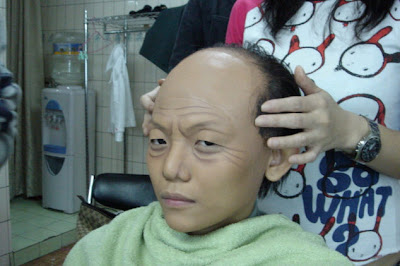 fake hair attach half of head to make it look like old man. More wrinkles added to the face