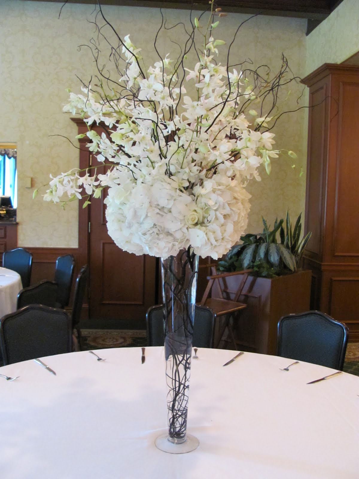 A black and white affair jm floral and event tall centerpiece white orchid spray coming out of the top with black culry willow sticks and a white hydrangea and rose cluster on a fluted vase with the reviewsmspy