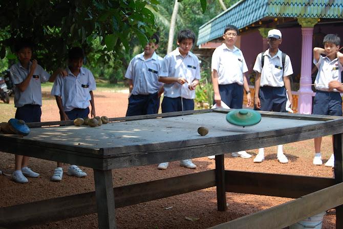 Pelajar-pelajar bermain gasing