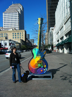 Alfie & I next to a colorful, 12-foot-tall statue of an electric guitar, in front of a busy street and high-rise buildings