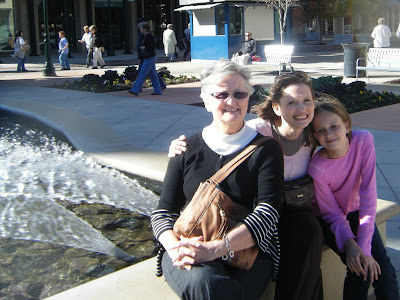 my Mom, daughter, and me sitting on the edge of a fountain, all are smiling as the breeze blows our hair back