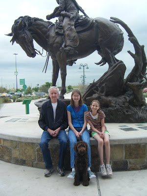 The kids, their Grandpa, and Alfie are seated at the base of an equestrian statue in front of Cabela's.