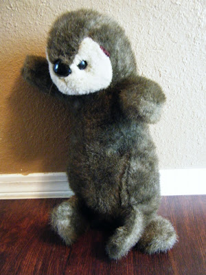 plush, chocolate-brown stuffed otter propped up against the wall; it has a cute white face but its left ear has been gnawed off