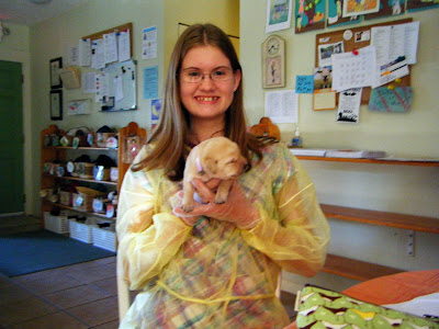 Charissa in yellow hospital gown and gloves holding an adorable little yellow lab puppy whose eyes are tightly shut; his face is roundish and wrinkly