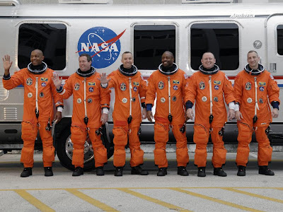 The STS-129 crew members line up beside the Astrovan