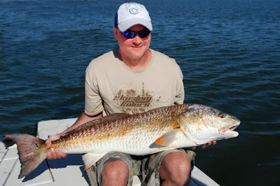 fisherman siting with big redfish