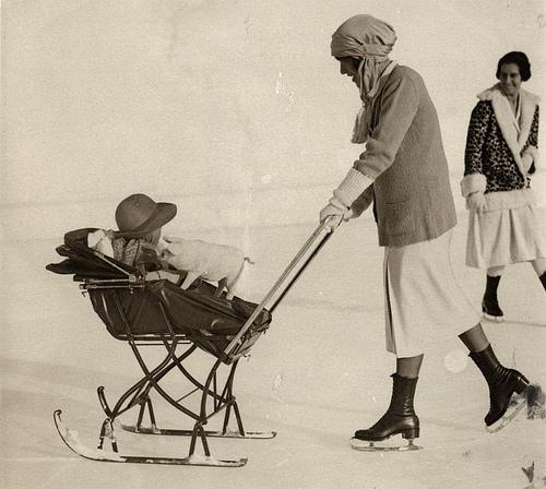 Pram on skis (sledge) on the ice, pushed by mom on skates. St. Moritz, Switzerland, 1926. Nationaal Archief / Spaarnestad Photo