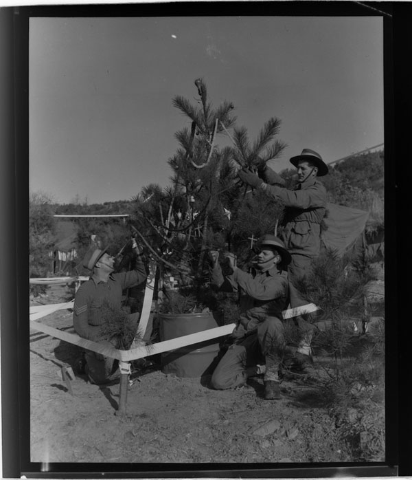 Christmas in Korea, 1953. The finishing touches are made to the Christmas tree at C Company, 3rd Battalion, The Royal Australian Regiment (3RAR), by Sergeant Alec Livermore of Chester Hill, NSW, the Company Sergeant Major (CSM); Private (Pte) Kev Keehan and Pte Peter Ferrier of Ringwood, Vic. This tree has electric lights powered by the Company generator which flash on and off at night.
