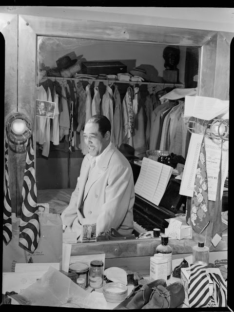 "Portrait of Duke Ellington, Paramount Theater, New York, N.Y., ca. Sept. 1946. Caption from Down Beat: Fifth in the series of staff lensman Bill Gottlieb's intimate dressing room shots of musical celebrities is Duke Ellington, with the mirror reflecting his always present piano, his conservative ties, his 20 suits, his 15 shirts, his suede shoes and his smiling self. Forms part of: William P. Gottlieb Collection (Library of Congress). In: ""Through the looking glass,"" Down Beat, v. 13, no. 20 (Sept. 23, 1946), p. 16."