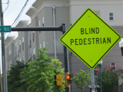 bright yellow sign that says Blind Pedestrian