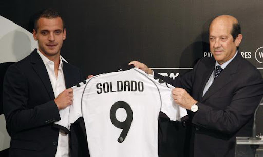 New Valencia player Roberto Soldado holds his shirt next to president Manuel Llorente