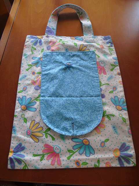 Bolsa de tela de flores con un gran bolsillo azul en el centro.