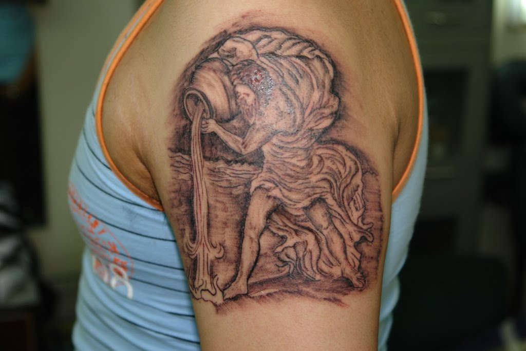 Full upper arm water bearer aquarius tattoo is a beauty