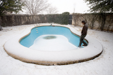An empty pool glows blue in rare desert snowstorm