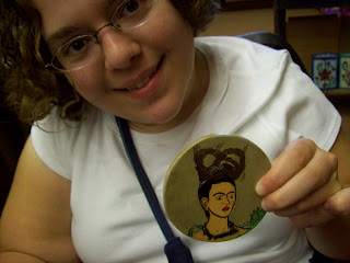 Sarah holding a coaster painted with a picture of Frida Kahlo